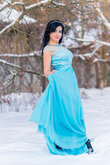 Greece woman in blue long romantic dress at snowy day, femininity and grace concept, winter fairytale