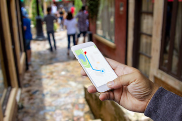 Hand holding mobile phone and searching for direction by map application in town.