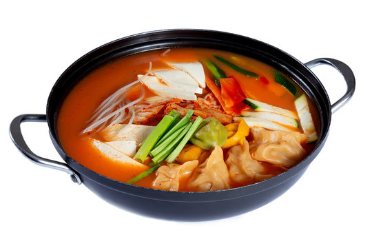Pan of traditional korean soup with tofu, noodles, dumplings and vegetables