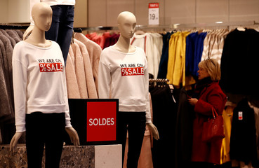 A woman shops in a store decorated with discount signs during the start of winter sales in Paris