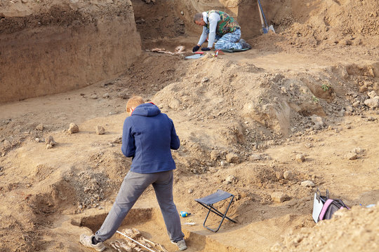 Archaeological excavations. The archaeologists in a digger process, researching the tomb with human bones, drawing the human remains. Real digger process. Outdoors, copy space.
