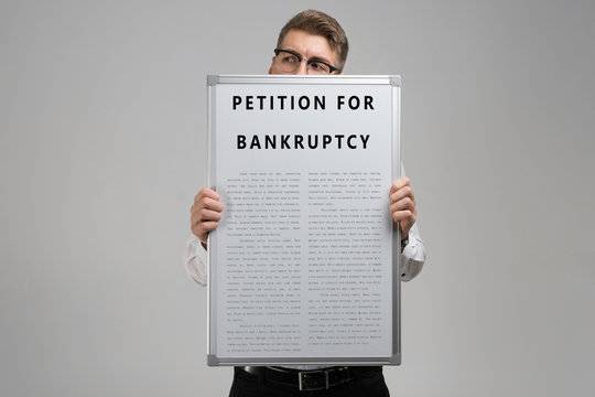 Young man keeps in front of him petition for bankruptcy isolated on light background