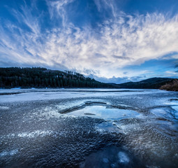 lake with an  ice in the winter evening time