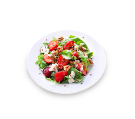 Salad with arugula, strawberries, goat cheese and walnuts isolated on white background with clipping path