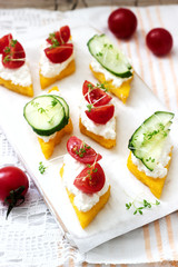 Vegetarian canapes from polenta with cheese, vegetables and cress on a light background. Rustic style.
