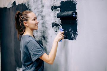 The girl repaints the gray wall in black