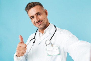 Portrait of happy medical doctor with stethoscope taking selfie photo, while standing isolated over blue background