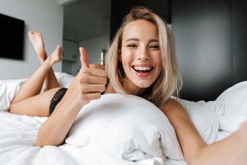 Image of adorable woman 20s wearing luxury lingerie smiling and taking selfie, while lying in bed on white linen in modern apartment
