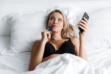 Image of european woman 20s wearing luxury lingerie holding smartphone and credit card, while lying in bed on white linen in cozy flat