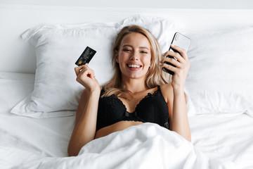 Beautiful cheerful young woman wearing lingerie laying