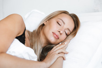 Young woman in lingerie underwear lies in bed at home sleeping.