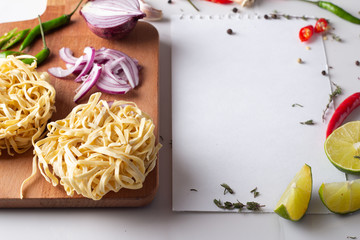 ingredients for Asian cuisine, hot pepper egg noodles and spices and a sheet of white paper.