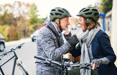 Active senior couple in love with electrobikes standing outdoors on a road in town.