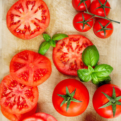 Various Fresh tomatoes with basil leaf on a cutting board, view from above