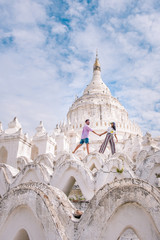 young couple on vacation in Myanmar visiting a old historical whitewashed white temple Buddhism in Mandalay ,  Mya Thein Tan Pagoda