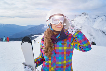 Woman Skier Standing at Snow Looking at Camera. Winter Montain background