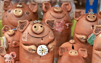 Brown ceramic piggy banks with painted hearts.