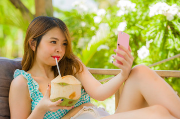 young happy and attractive Chinese student girl at tropical resort garden drinking coconut water taking selfie photo with mobile phone camera enjoying holidays trip
