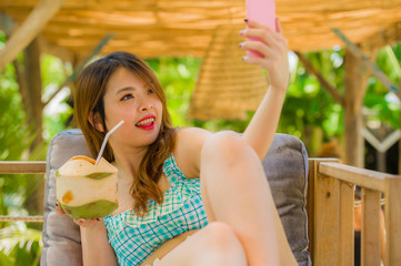 young happy and attractive Korean student girl at tropical resort garden drinking coconut water taking selfie photo with mobile phone camera enjoying holidays trip