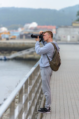 young man with SLR camera photographs the sea