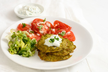 vegetable broccoli pancakes with yoghurt dip, lettuce and tomato, healthy slimming food, white plate on a white table,