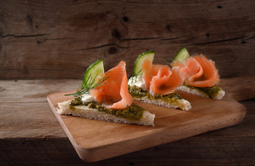 canapes in a row with smoked salmon, cucumber, pesto, cream and dill garnish on a rustic wooden board, copy space, close up