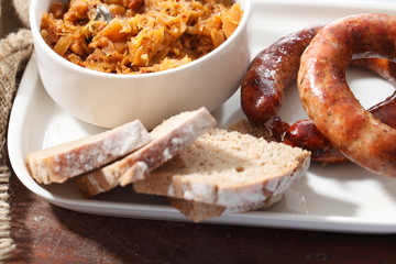 Bigos tradycyjny z pieczoną białą kiełbasą i pieczywem.