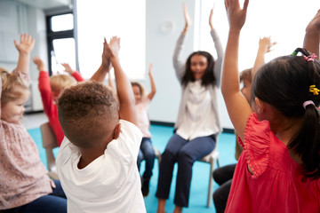 A class of infant school children sitting on chairs in a circle in the classroom, raising hands...