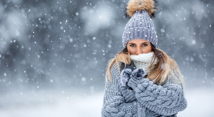 Portrait of young beautiful woman in winter clothes and strong snowing. Wall mural