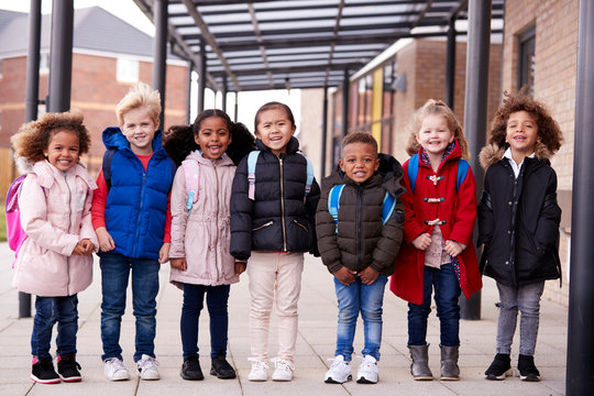 A group of smiling young multi-ethnic school kids wearing coats and carrying schoolbags standing in a row in walkway outside their infant school smiling to camera, full length, front view