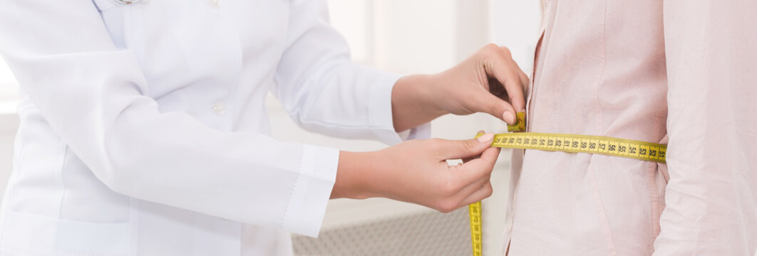 Nutritionist measuring bmi of patient in office