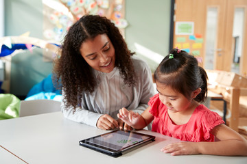 Female infant school teacher working one on one with a Chinese schoolgirl, sitting at a table in a classroom using a tablet computer, close up