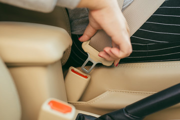 Cropped image of a woman sitting in car and putting on her seat belt