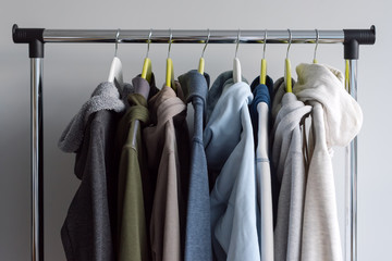 Hanger stand with spring or autumn warm clothes on grey background. Cold season, cozy sweaters and hoodie on hangers