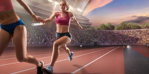 Female athletes sprinting. Runner passes the baton at the running track in professional stadium - fototapety na wymiar