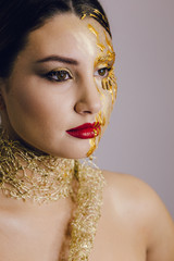 beautiful art makeup on model face, studio shot. Golden paint, red lips