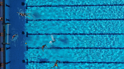 Aerial drone top view photo of people swimming in pool