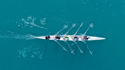 Aerial drone bird's eye view of sport canoe operated by team of young men in open sea