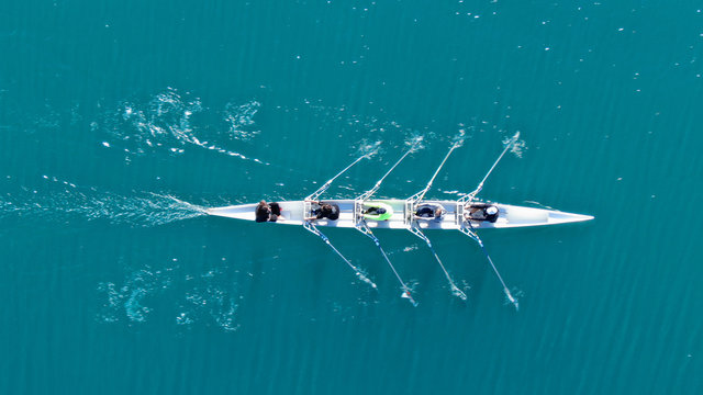Aerial drone bird's eye top view of sport canoe operated by team of young men in open sea