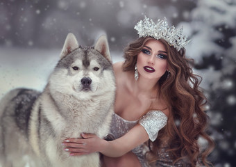 Portrait of woman in silver dress and crown as snow Queen, in winter forest with Husky dog .The fairy Princess and the wolf in the winter.