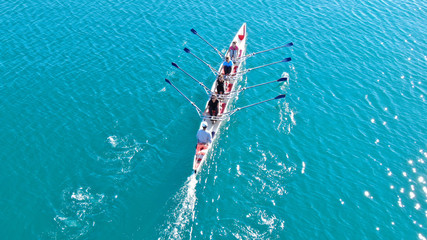 Aerial drone bird's eye view of sport canoe operated by team of young women in emerald clear sea
