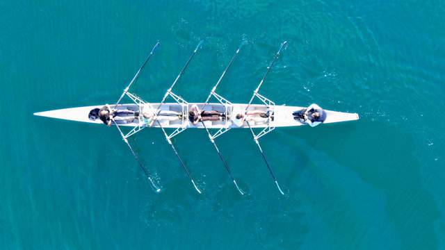 Aerial drone top down view of sport canoe operated by team of young women in emerald clear sea
