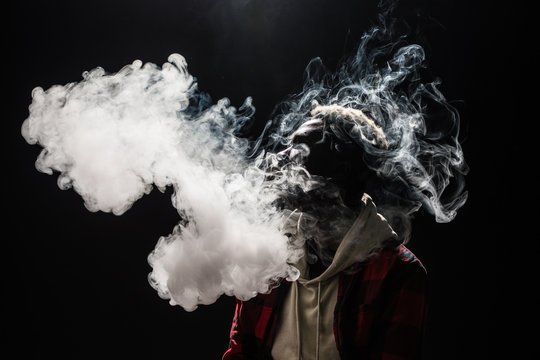 Feeling relaxed. Portrait of afro guy holding vape device and surrounded by cloud of smoke isolated on black background
