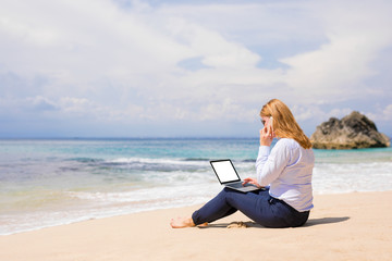 Business woman working on the beach
