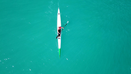 Aerial drone bird's eye view of sport canoe operated by young fit man in emerald clear waters