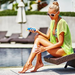 Woman applying sunscreen on her legs