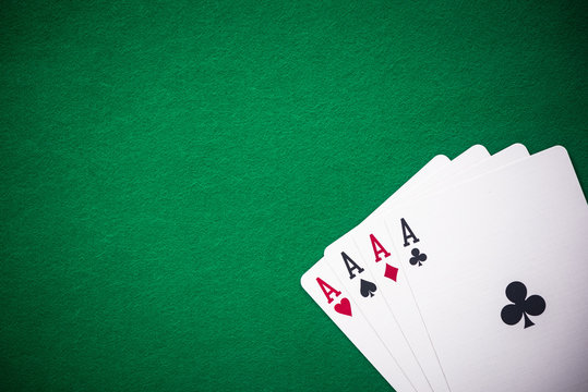 Four aces folded on green casino table, copy space