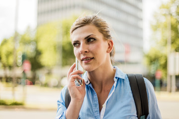 Portrait of woman with backpack in the city talking on cell phone