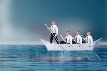 Leader Lead his Team Paddling on Boat of Paper