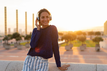 Spain, Barcelona, Montjuic, smiling young woman listening to music with headphones at sunset